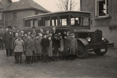 Kinder und Erwachsene stehen vor einem Bus
