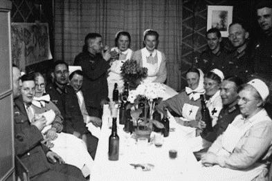 Arzthelferinnen und Soldaten sitzen um einen Tisch und trinken aus Flaschen